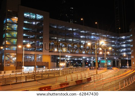A lit parking garage in the city. - stock photo