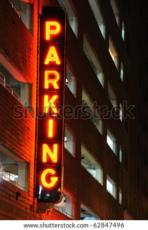 A lit parking sign at a parking garage. - stock photo