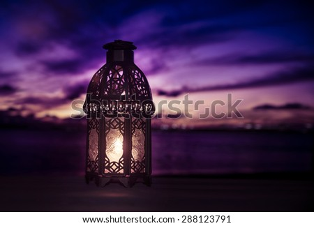 A lit up ramadan lamp against serene and beautiful evening sky. Ramadan background. - stock photo