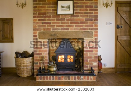 A lit wood burning stove in a farmhouse lounge - stock photo