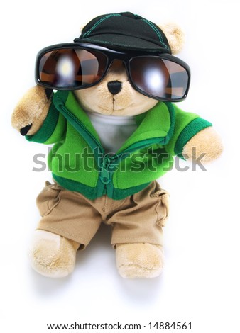 A little adorable teddy bear is wearing big sunglasses, a green jacket, brown pants, a hat and it's isolated on white background. - stock photo