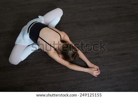 A little adorable young ballerina doing stretching exercises on the floor. Ballet,  gymnastics, free callisthenics. - stock photo
