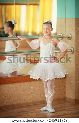 A little adorable young ballerina in a white tutu near the mirro