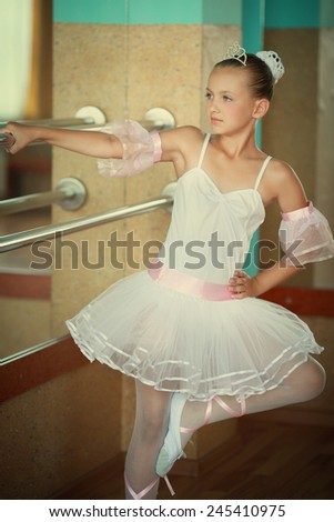 A little adorable young ballerina in a white tutu near the mirror