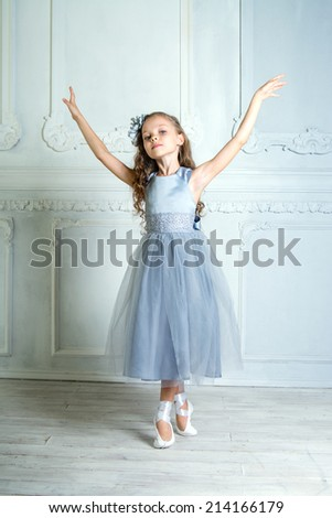 A little adorable young ballerina is posing on camera in the interior studio  - stock photo