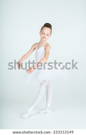 A little adorable young ballerina poses on camera