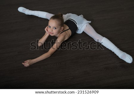 A little adorable young girl doing stretching exercises on the floor. Ballet,  gymnastics, free callisthenics. - stock photo