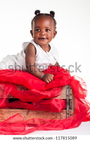 A little African baby laying in a wooden crate. - stock photo