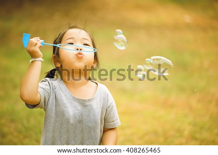 A little asian girl blowing soap bubbles, closeup portrait beautiful curly baby - stock photo