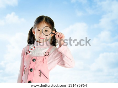 A little Asian girl peers at the camera through a magnifying glass in summer day, blue sky background