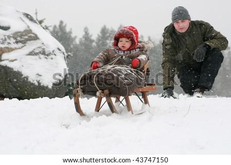 A little baby boy sledding - stock photo