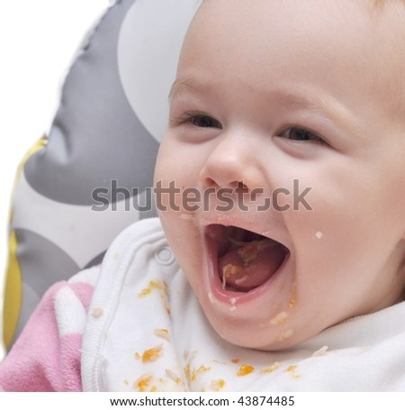 A little baby eating spinach, expressing that she does not like it, the mother feeding her. - stock photo