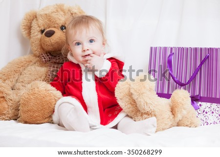 A little baby girl dressed red fancy Santa Claus dress with violet paper bag for gifts and big teddy bear