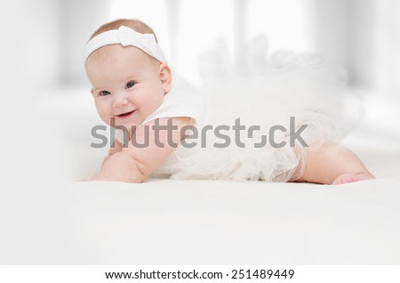 A little Baby girl in a white dress with a smile on my face - stock photo