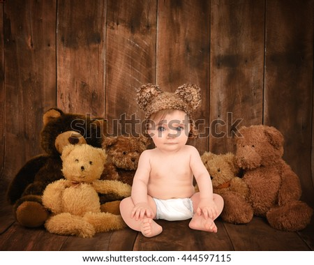 A little baby in a hat is sitting with teddy bear friends on a wood background for a love, family or photography concept.