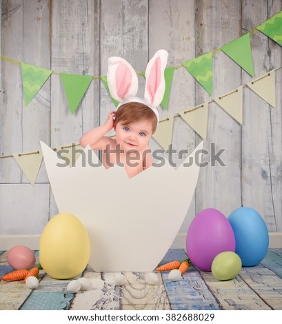 A little baby is sitting on an open easter egg hatched for a seasonal portrait or photography concept. - stock photo