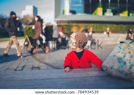 A little baby is standing in the city with crowds of people walking past