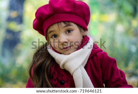 A little beautiful girl with big eyes, looks surprised, warm in autumn, in a pink beret and coat