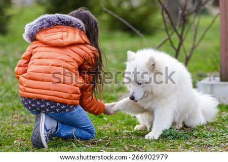 A little beautiful girl with her pet dog outdoors in park - stock photo