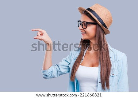 A little bit! An isolated shot of an attractive young woman indicating size with her hand while standing against grey background - stock photo