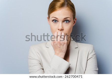 A little bit nervous. Nervous young businesswoman biting her nails while standing against grey background - stock photo