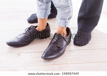 A little bit oversized. Close-up of child wearing large shoes while his father standing in socks near him  - stock photo
