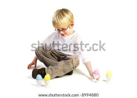 a little blond boy is playing with easter eggs - stock photo
