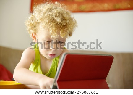 a little blond child looking at a digital tablet