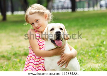 A little blond girl with her pet dog outdooors in park - stock photo