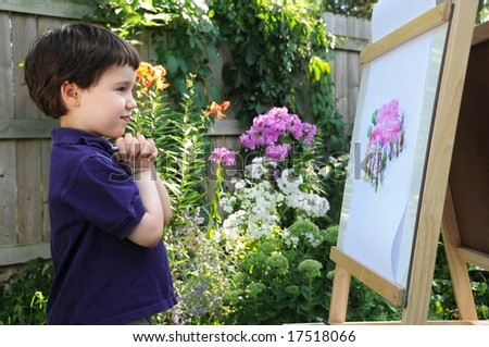 A little boy admires his painting of a phlox seen in the flower garden next to him - stock photo