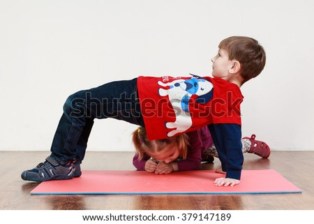 A little boy and a girl are doing an exercise at the gym - stock photo