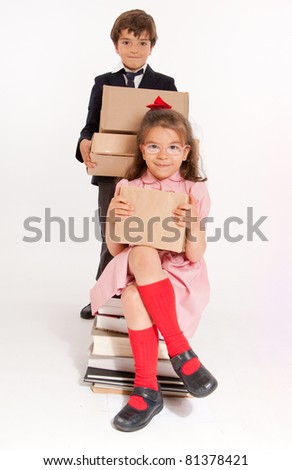 A little boy and girl in school clothes with a pile of books and boxes - stock photo