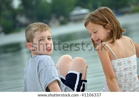 a little boy and girl make funny faces on a summer day at the lake - stock photo