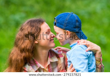 A little boy and his mother look at each other and laugh. Family composition - stock photo