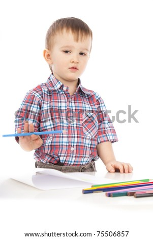 A little boy at the table draws with colored pencils on white background isolated