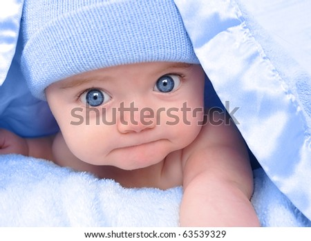 A little boy baby is hiding under a blue blanket with a hat on. He is staring at the camera and posing on his tummy. Use it for a childhood, parenting or love concept.