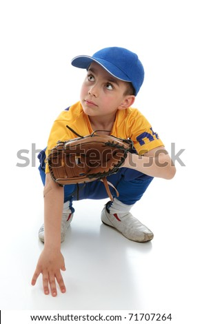 A little boy baseball player crouching down with a mitt.  Space for copy. - stock photo