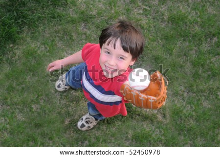 A little boy catches a fly ball during a baseball game - stock photo