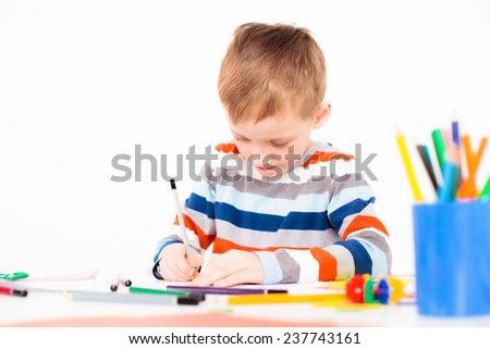 A little boy concentrated on drawing a picture