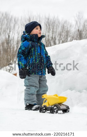 A little boy dressed in a snowsuit is outside standing beside a yellow toy dump truck in a cleared snow path he is trying to see over a deep snowbank beside of him.  - stock photo