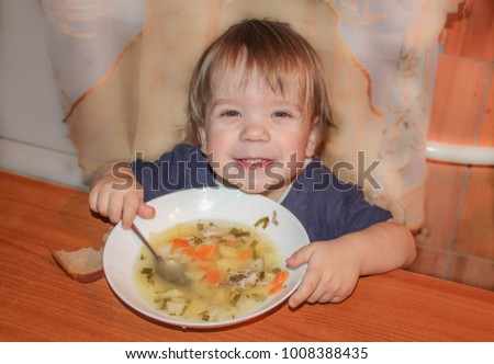 A little boy eats soup on his own. The child learns to eat from the plate. Children in the kitchen.