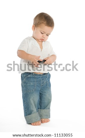 A little boy experimenting with a cellphone - stock photo