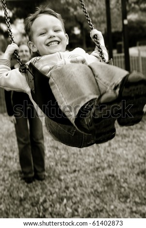 A little boy having a great time on a swing in a playground - stock photo
