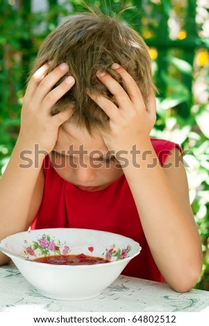 A little boy holding his hands behind his head and looks at his food - soup - stock photo