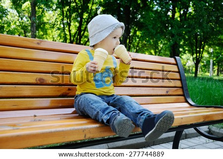 a little boy holding two ice creams - stock photo