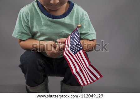 A little boy holds an American flag and smiles. - stock photo