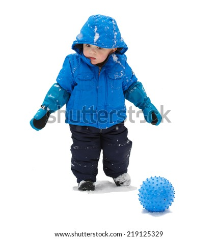 A little boy in a blue snowsuit is standing beside a blue toy ball on a snowy day.  Isolated on a white background.  - stock photo