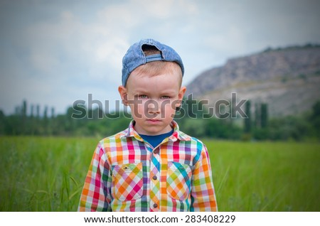 A little boy in a cap and a multicolored plaid shirt looking sad in front of him. Family composition