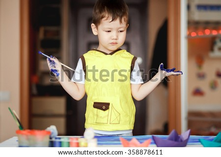 A little boy in a yellow T-shirt stained with paint after the painting does not know what to do. - stock photo