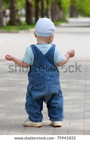 A little boy in denim jumpsuit and cap, standing on the track in the park